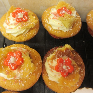 Vanilla Sponge cupcakeswith a red flower decoration